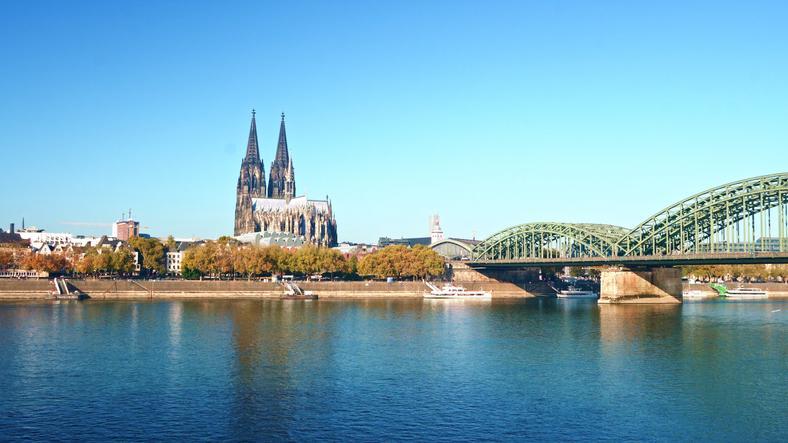Blick vom Rhein auf den Kölner Dom und die Hohenzollernbrücke bei blauem Himmel