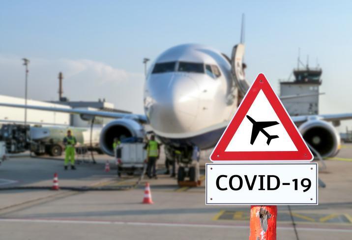 Flugzeug am Flughafen mit Warnschild COVID-19 davor