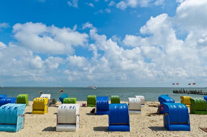 Bunte Strandkörbe am Strand mit dem Meer im Hintergrund. Steg mit Flaggen auf der rechten Seite, Schiffe in der Ferne