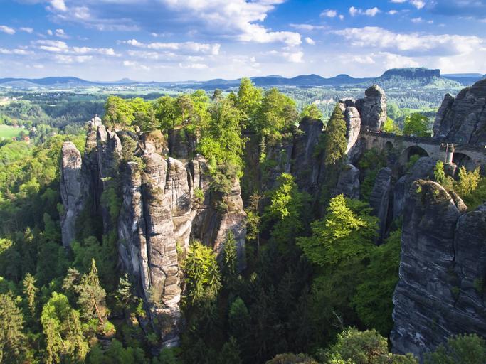 Die Felsen der Bastei von oben mit grüner Landschaft und Bergen im Hintergrund bei blauem Himmel mit einzelnen Wolken