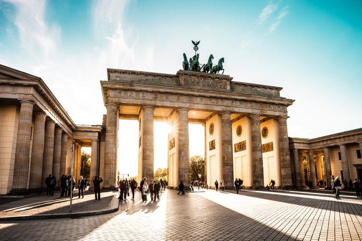 Brandenburger Tor mit blauem Himmel und Sonne, die hindurch scheint