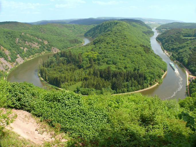 Eine große Kurve der Saarschleife mit Waldlandschaft von oben. Auf dem Fluss fährt ein Schiff